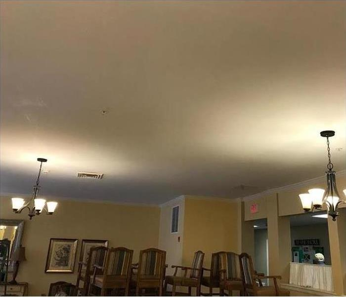 wet ceiling with water stains and stacked chairs in dining area
