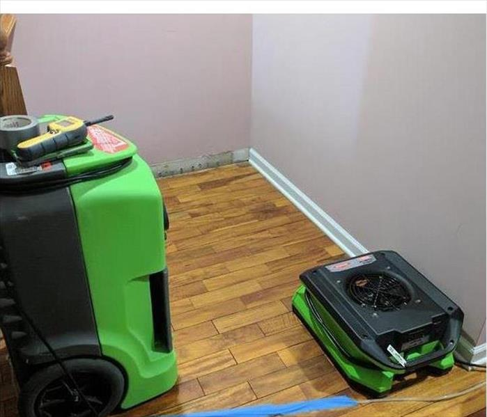 SERVPRO equipment with hardwood flooring and wall without a baseboard