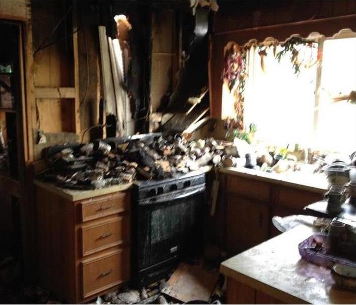 Kitchen with heavy fire damage and debris on the stovetop