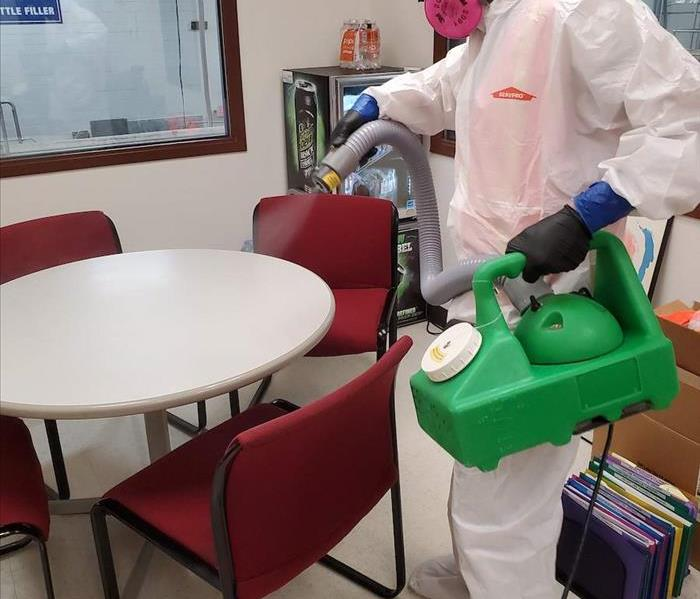A SERVPRO employee with a white suit on spraying a table.