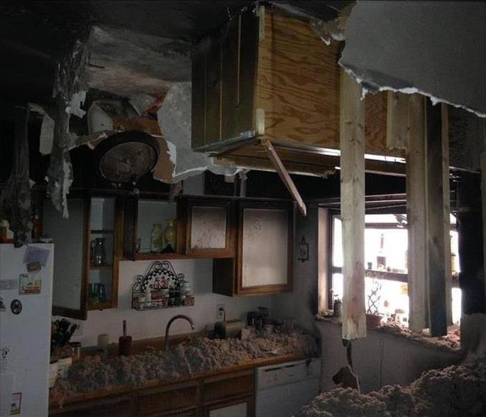 ripped open ceiling, insulation on the counters, hint of fire damage