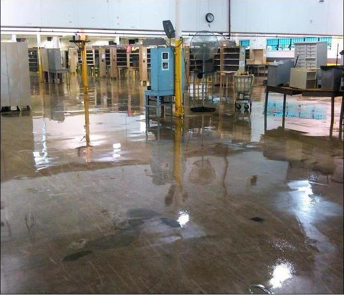 concrete floor with water reflecting from a flood with equipment spread out in a warehouse