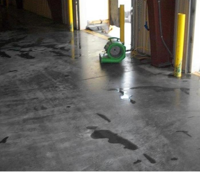 green air mover, small puddle of water, three yellow collision poles in a bay door extrance