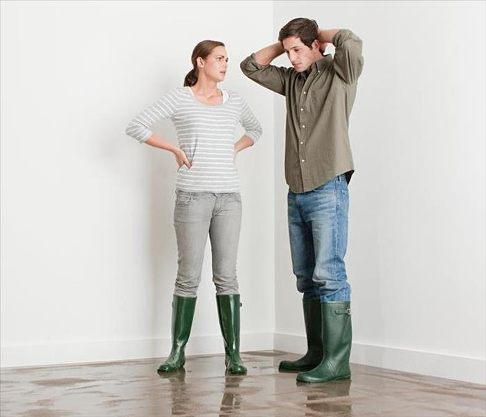 Two people standing in a room with green rain boots on.